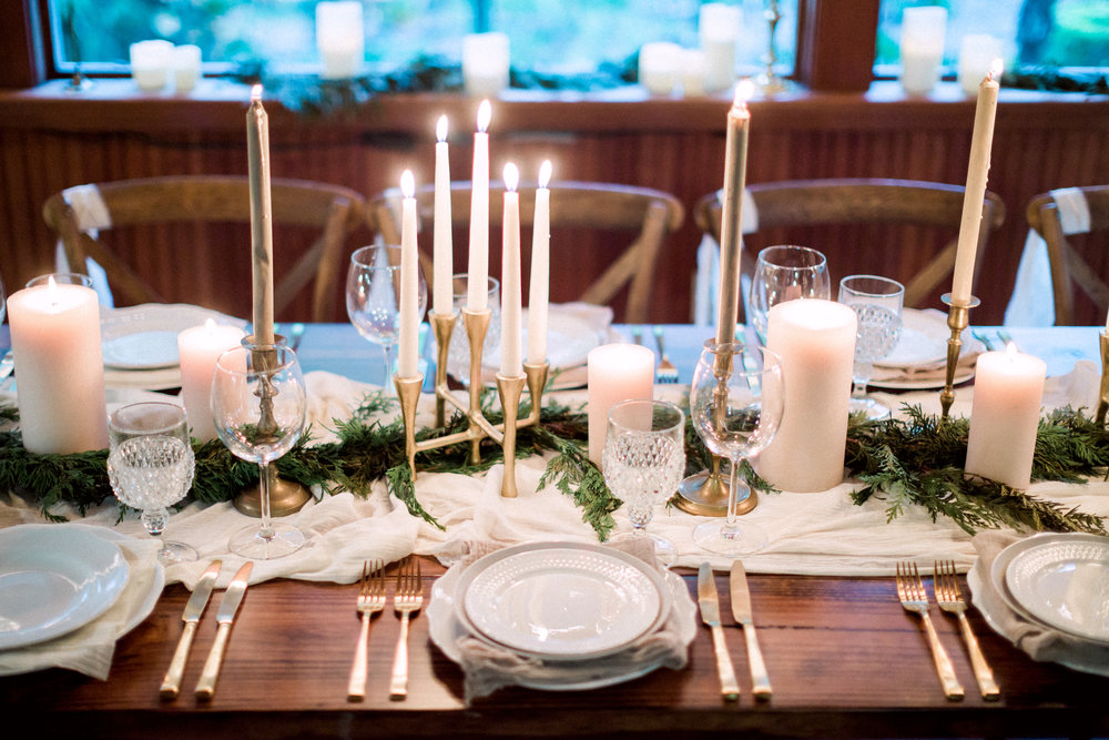 Candle and greenery centerpiece on a wooden farm table