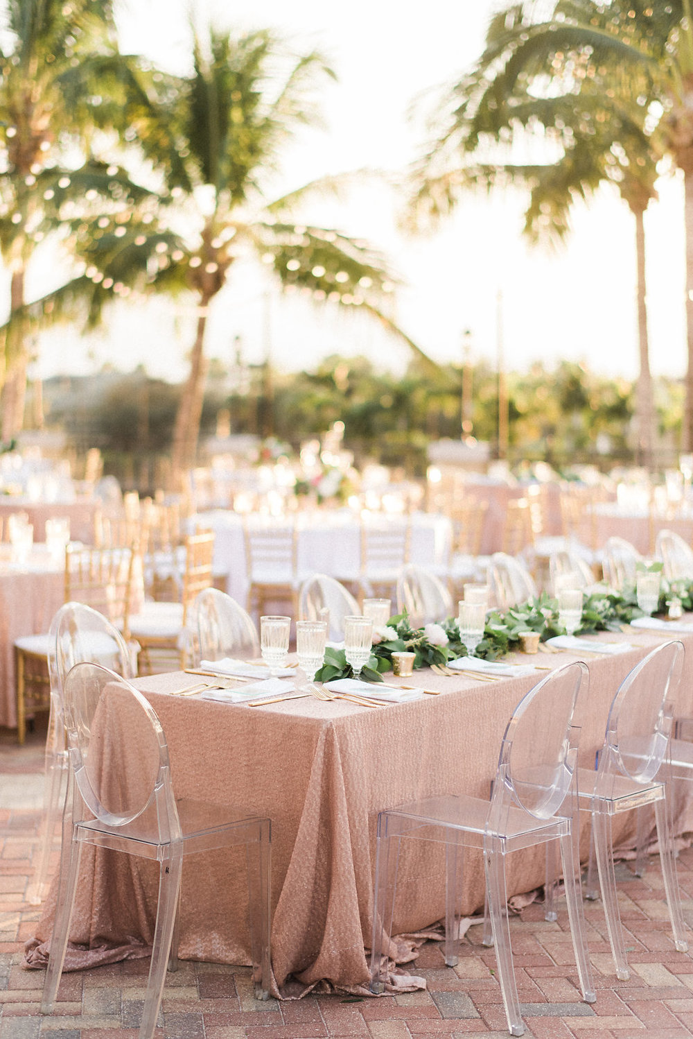 Blush and Gold wedding reception with garland centerpiece and ghost chairs