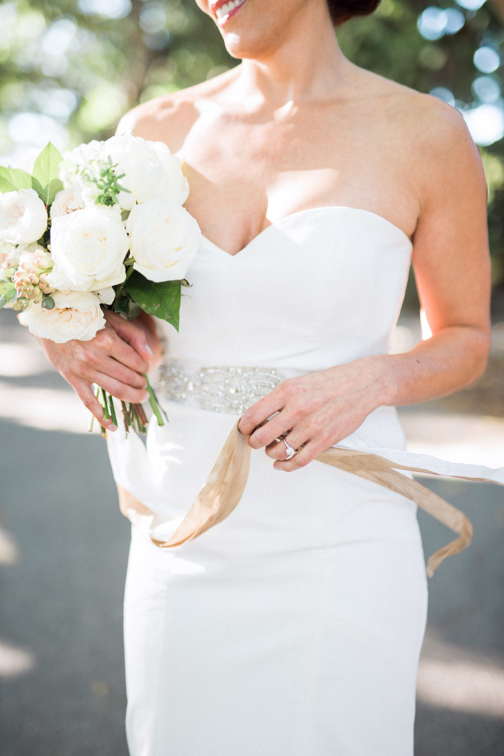 bride holding a white, garden style bouquet wearing a fitted silk wedding dress