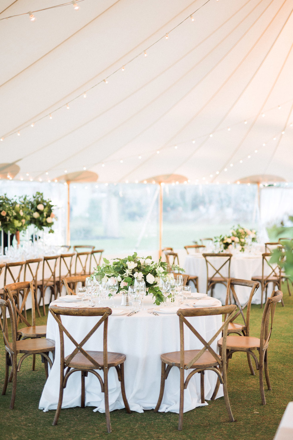 Tented wedding reception with French country wood chairs, garden style florals with greenery.