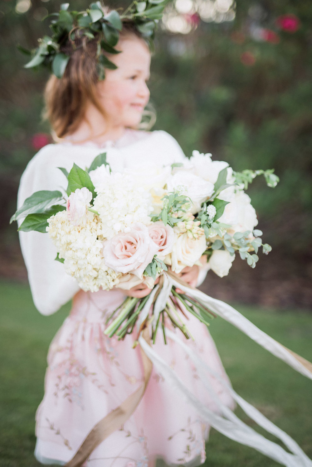 Flowergirl holding gorgeous white and blush garden style bouquet with roses and eucalyptus