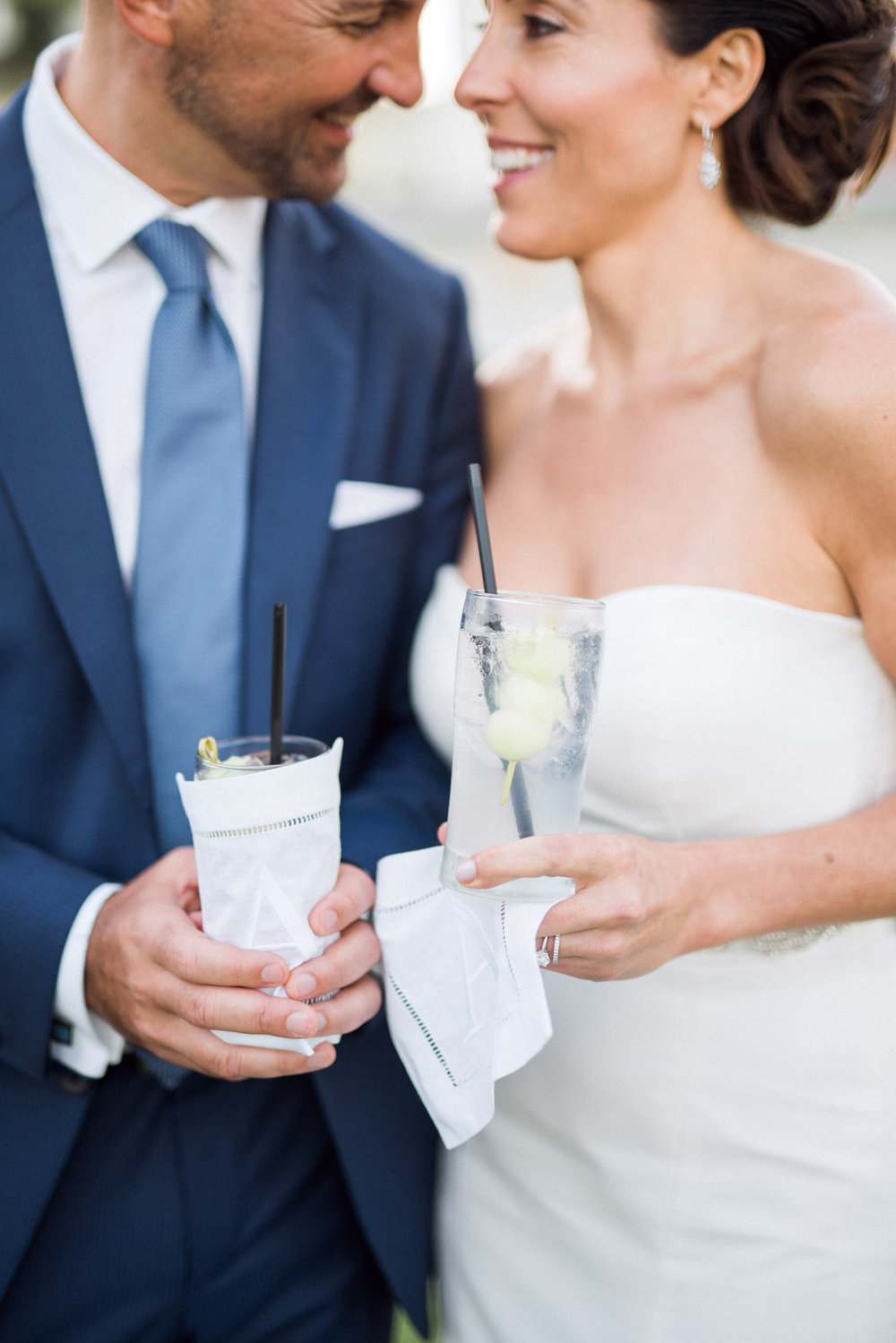 bride and groom holding cocktails in monogramed hemstich napkin at wedding reception