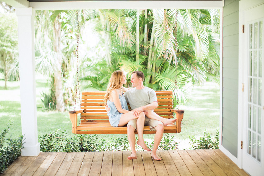 Engagement photo of future bride and groom on their porch swing at home