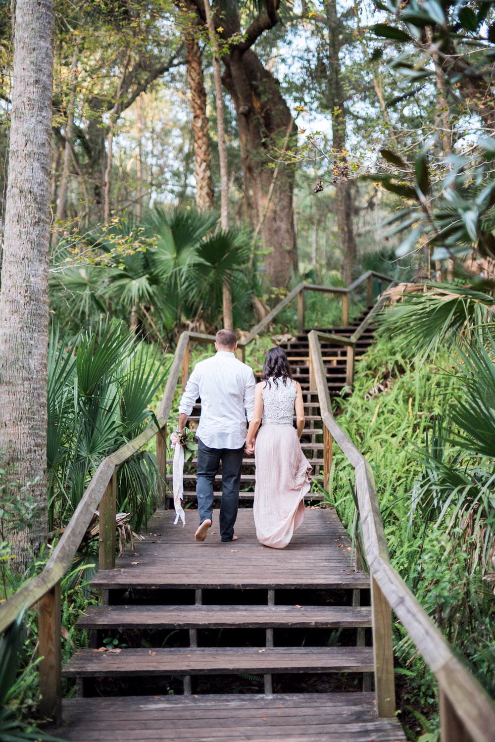 Future bride and groom holding hands during engagement session/ photos at Wekiwa Springs State Park