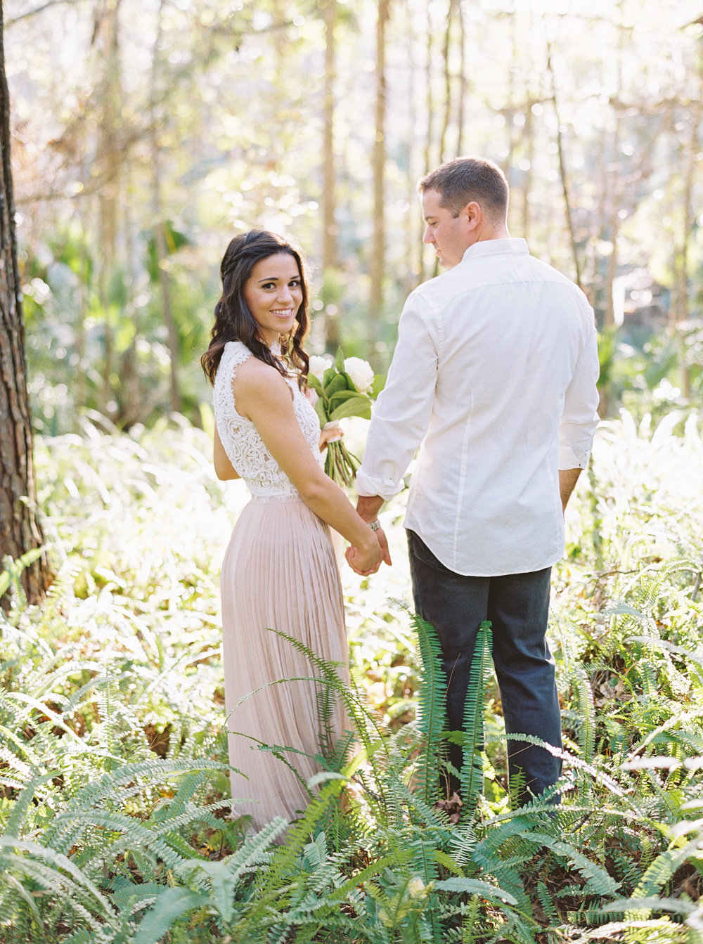 Bride and groom holding hands for styled engagement session photos at Wekiwa Springs State Park. Bride wearing Morning Lavender blush pink pleated maxi skirt and beaded, lace top.