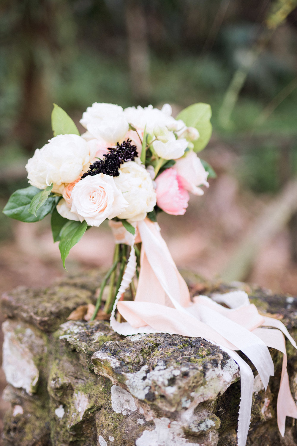 Free form, loose, garden style bridal bouquet created with peonies and roses in blush and white, with loose, free flowing silk ribbon around the clutch. Created by wedding planner, designer and florist, Elleson Events in Naples, FL