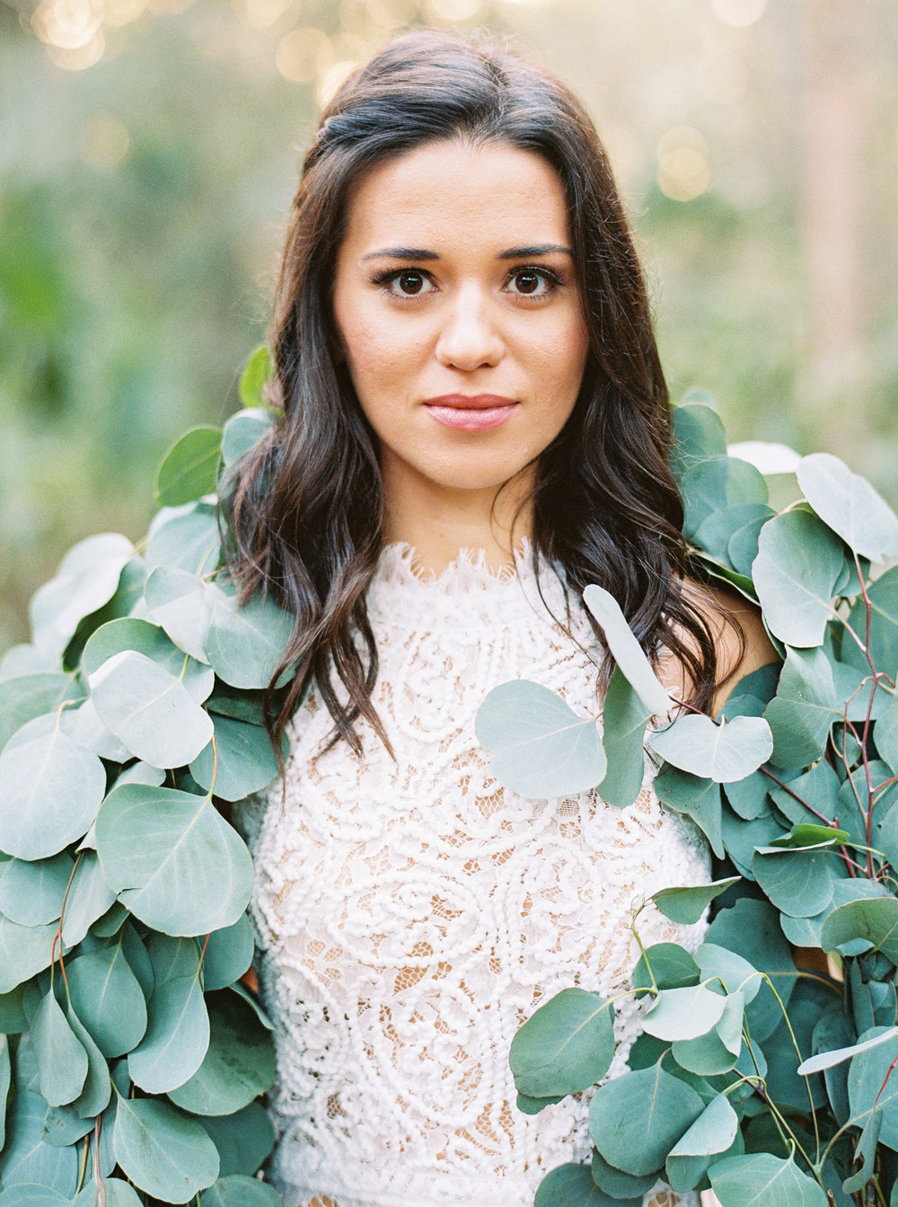 Bride holding eucalyptus garland instead of a bouquet. Floral styled shawl. Greenery garland used as floral shrug.