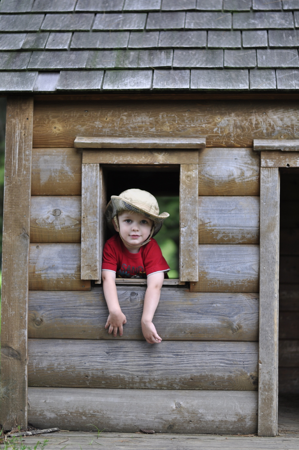 Hudson Klear peeks out from a little cabin at Valle Crucis Park.  Photo by Athalia Whitworth.