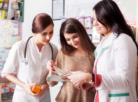 Woman assisted by pharmacist and doctor