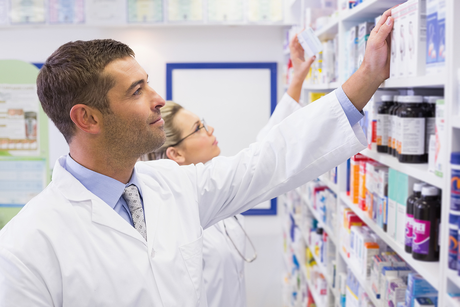 Pharmacist stocking medicine in local pharmacy