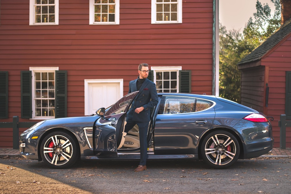 Suit: Indochino, Shoes: Johnston & Murphy, Glasses: Burberry, Sweater: Ralph Lauren, Car: 2010 Porsche Panamera Turbo courtesy of Foreign Cars Italia Greensboro, Photo: Alec Hutchins Photography.