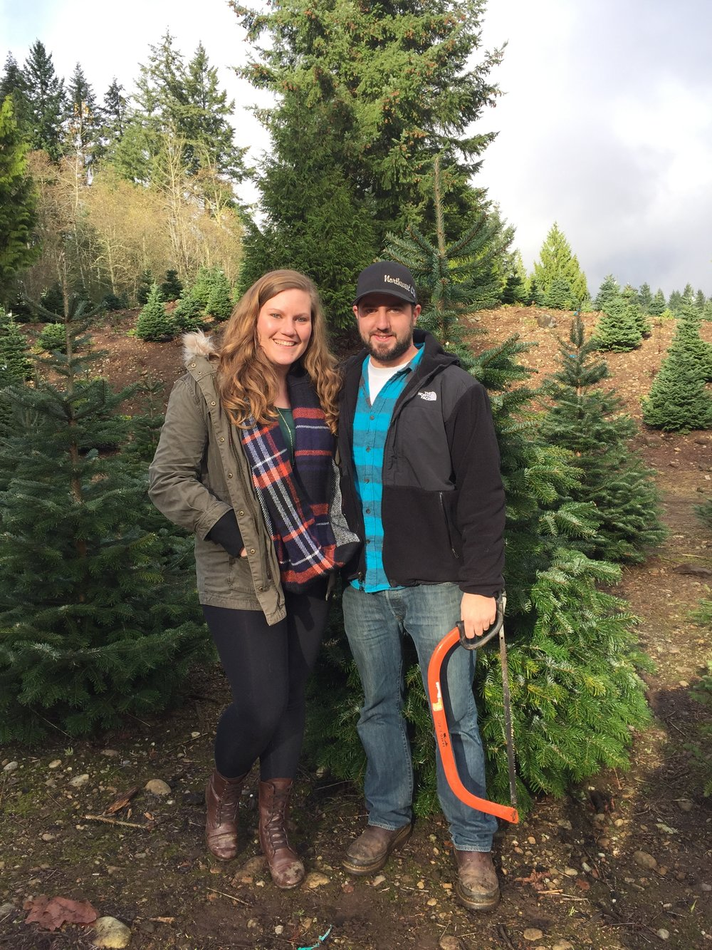 Photo of my fiance and I cutting down our first Christmas tree in our new house at Trinity Tree Farm!
