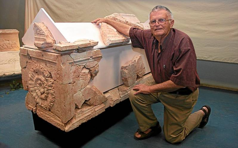 Archaeologist Ehud Netzer with the remnants of the red sarcophagus
