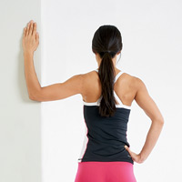 Stand next to a doorway or the protruding corner of a wall. Place the forearm and elbow against the side of this door frame or wall, with a 90 degree angle at both your upper arm and forearm. Now slowly lean your body forward, keeping your shoulder stable and being sure not to rotate your shoulder forward.