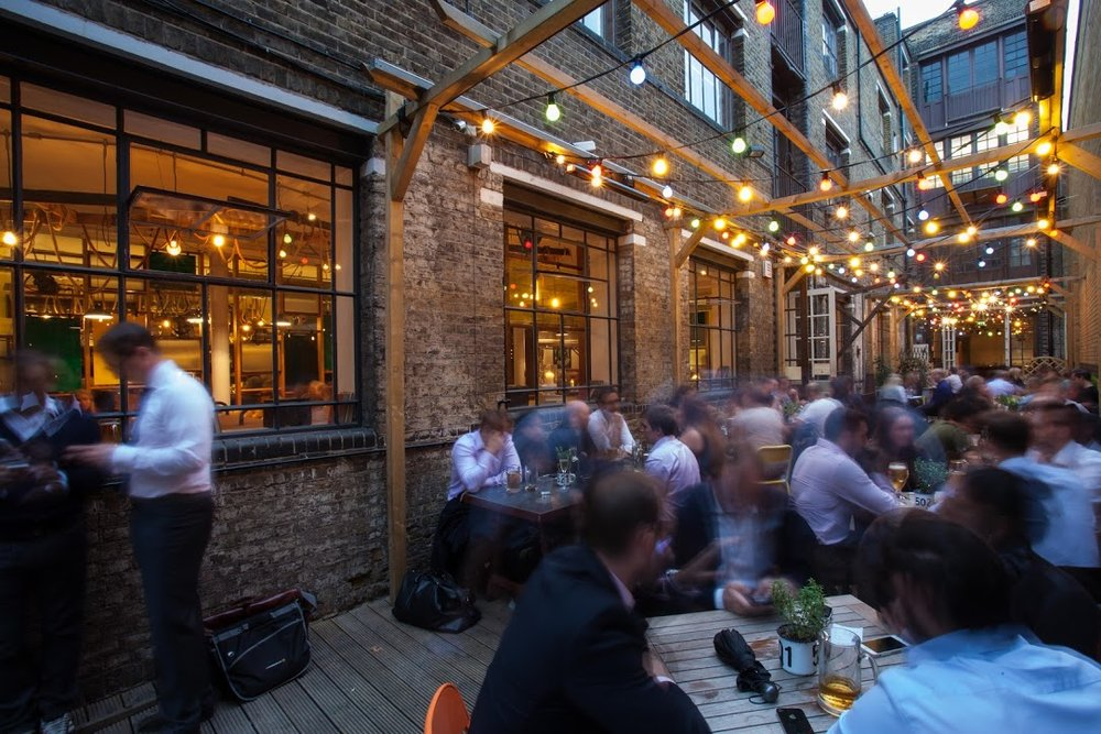 Tanner & co exterior, the yard on a busy night, lit with fairy lights hanging from a wooden framework suspended high above the tables