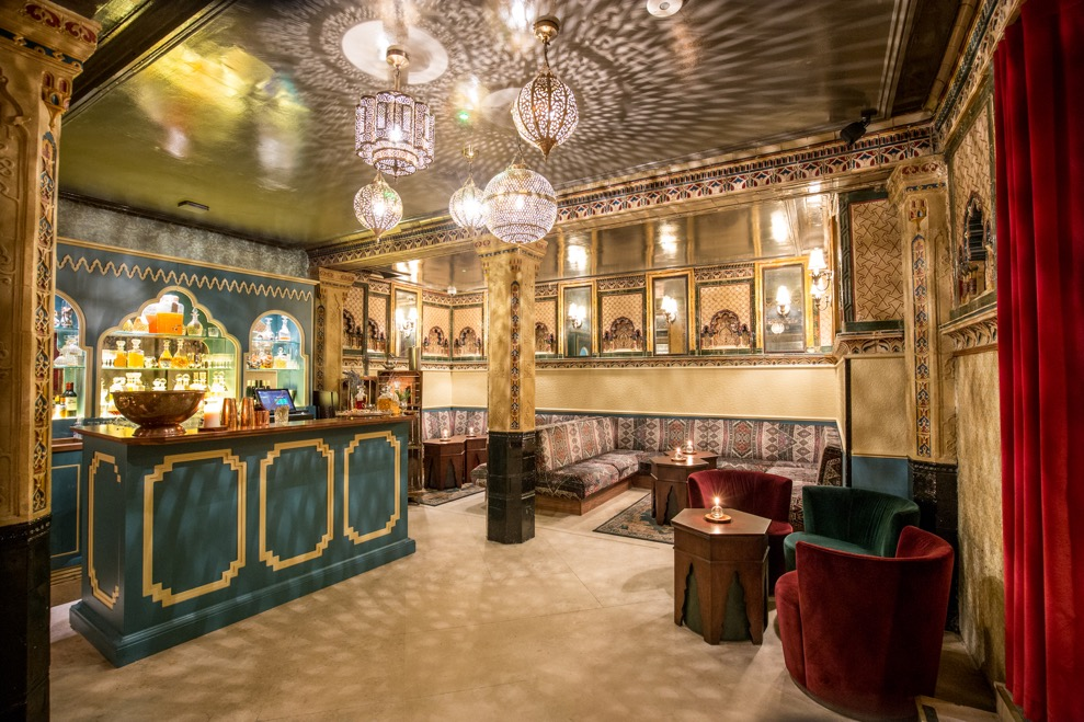 Victorian Bath House interior, richly patterned walls and furniture with chandeliers hanging from an ornate ceiling