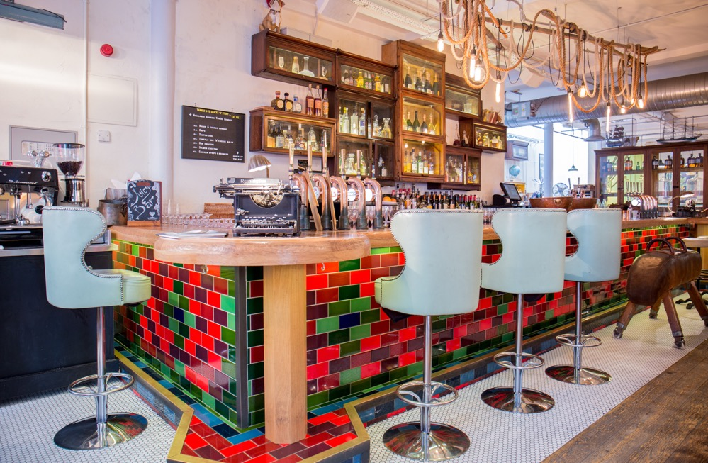 Tanner & co interior, seating at the bar: blue leather upholstered bar stools with backs