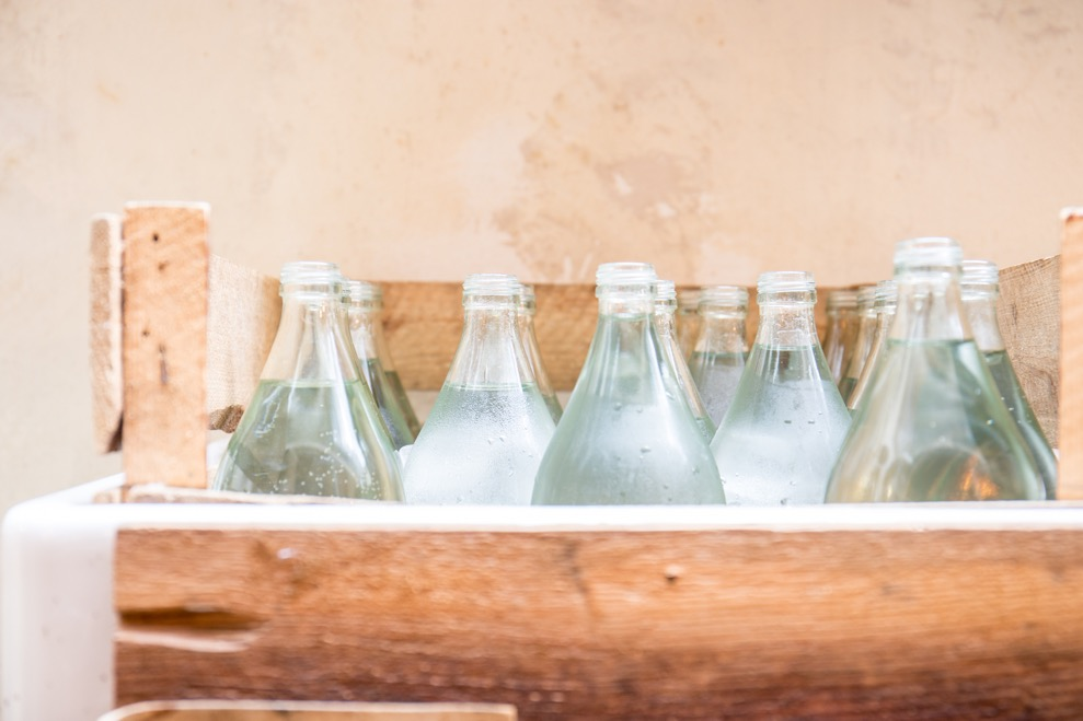 Tanner & co interior, a dozen glass water bottles in a rough wooden box