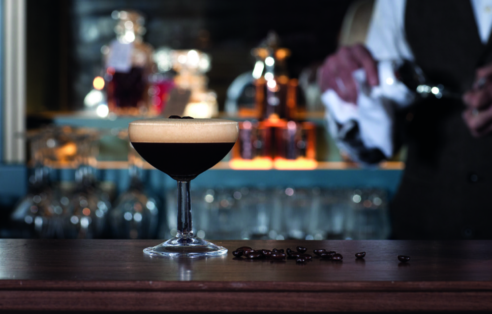 A dark cocktail with a creamy top in a shallow glass