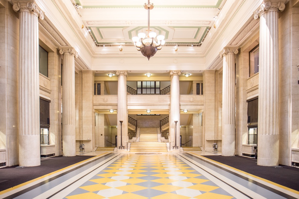 Banking Hall interior, the banking hall, empty: a high-ceilinged room framed by ionic columns, with polished marble floor and large chandelier