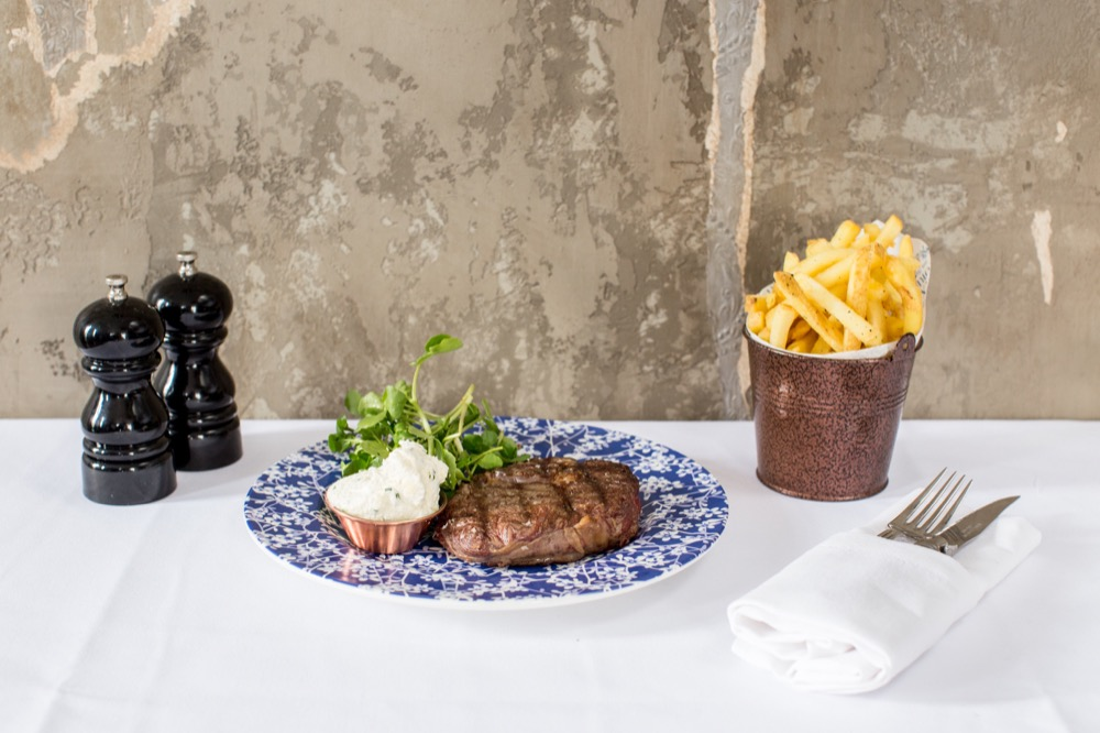 Six Storeys interior, steak and rocket on a blue and white flower-patterned plate, with a metal pail of chips