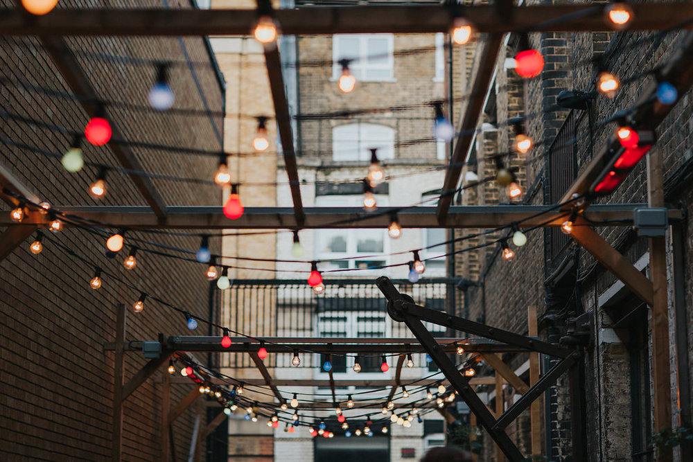 Tanner & co exterior, red, orange, blue and green fairy lights hanging from a wooden framework suspended high above the tables in the yard