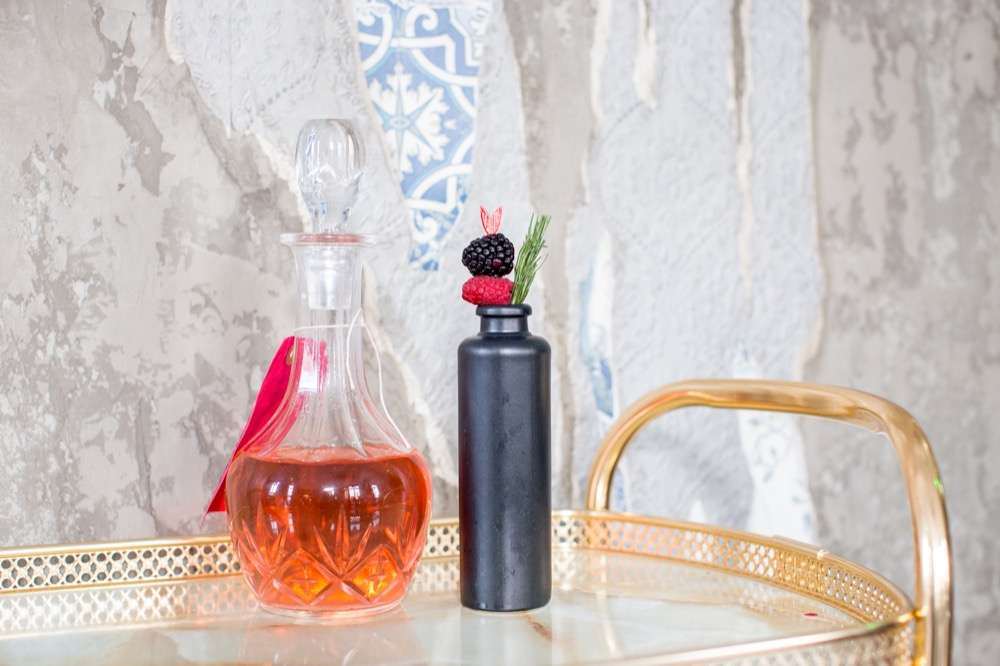 a decanter of infused gin and a tall dark bottle garnished with summer fruits and a sprig