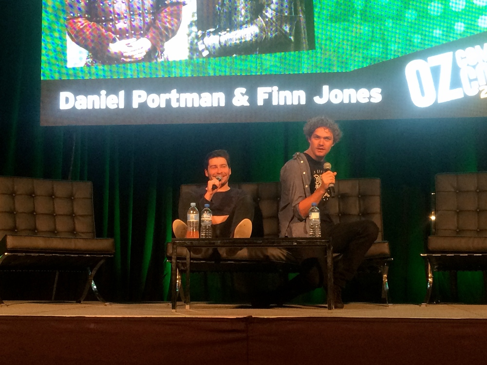 Finn Jones striking a pose for the photographing crowd, Daniel Portman seems amused.