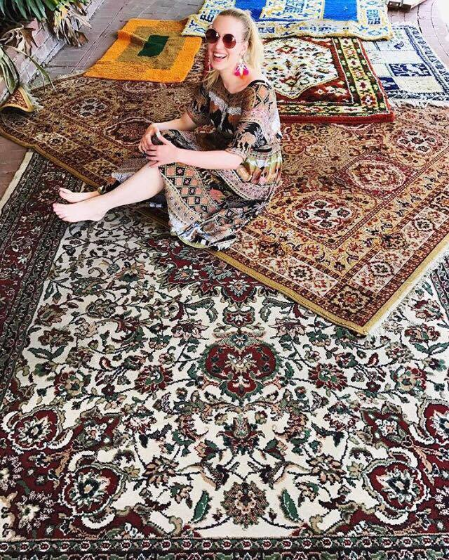 A happy Hannah surrounded by rugs that will be in store