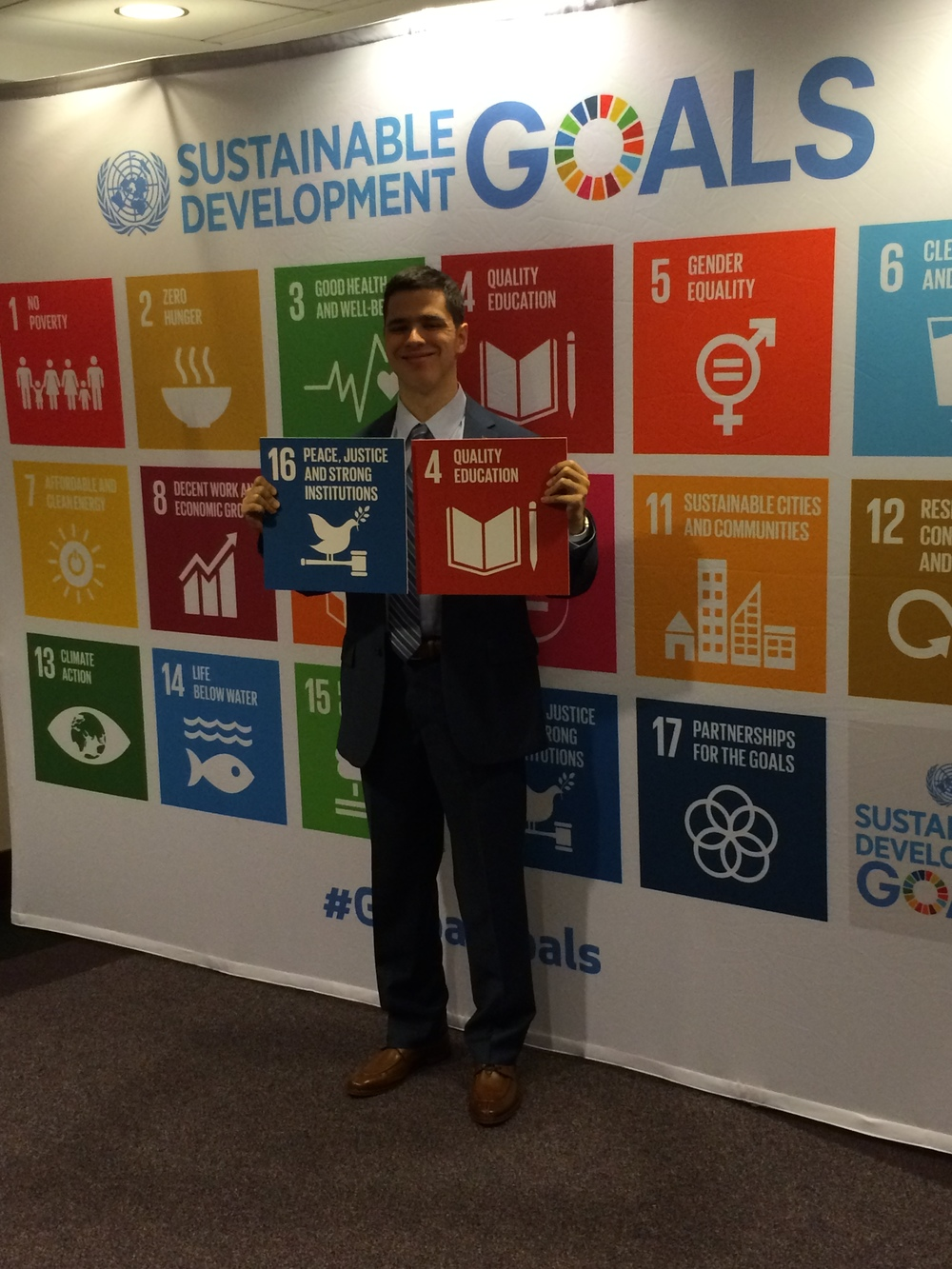 Pierce Lowary holding up his 2 favorite UN Global Goals