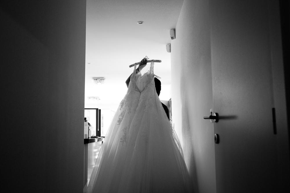 Jessica en Sandy kenden de huwelijksfotografen van is800 nog van bij hun verlovingsshoot, en toen wisten we al: dat komt meer dan goed. Deze twee lieverds halen het beste uit hun Belgisch-Chinees-Filipijnse roots en combineren dat tot wie ze zijn: een schitterend koppel. We reden van de ceremonie in de Spiegelzaal op de Meir in een riksja richting het Centraal Station, om daarna het feest passioneel verder te zetten in feestzaal Horta. Zwart-wit foto van de bruid die haar jurk binnendraagt.