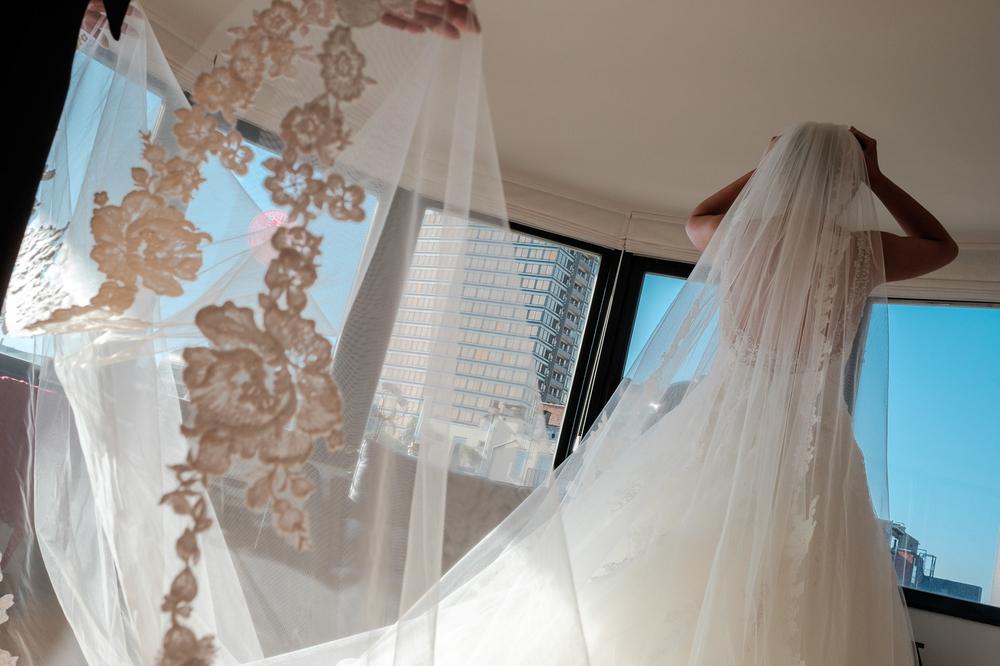 Jessica en Sandy kenden de huwelijksfotografen van is800 nog van bij hun verlovingsshoot, en toen wisten we al: dat komt meer dan goed. Deze twee lieverds halen het beste uit hun Belgisch-Chinees-Filipijnse roots en combineren dat tot wie ze zijn: een schitterend koppel. We reden van de ceremonie in de Spiegelzaal op de Meir in een riksja richting het Centraal Station, om daarna het feest passioneel verder te zetten in feestzaal Horta. Zwart-wit foto van de bruid die haar jurk binenndraagt.