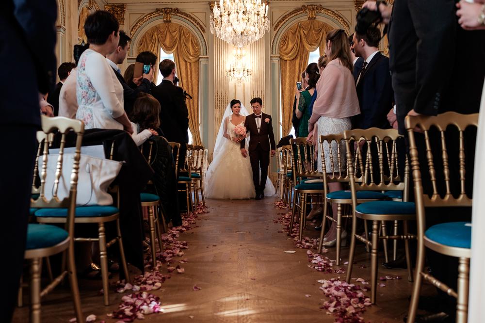 Jessica en Sandy kenden de huwelijksfotografen van is800 nog van bij hun verlovingsshoot, en toen wisten we al: dat komt meer dan goed. Deze twee lieverds halen het beste uit hun Belgisch-Chinees-Filipijnse roots en combineren dat tot wie ze zijn: een schitterend koppel. We reden van de ceremonie in de Spiegelzaal op de Meir in een riksja richting het Centraal Station, om daarna het feest passioneel verder te zetten in feestzaal Horta. De bruid treedt de ceremoniezaal binnen, het gangpad is versierd met bloemblaadjes.