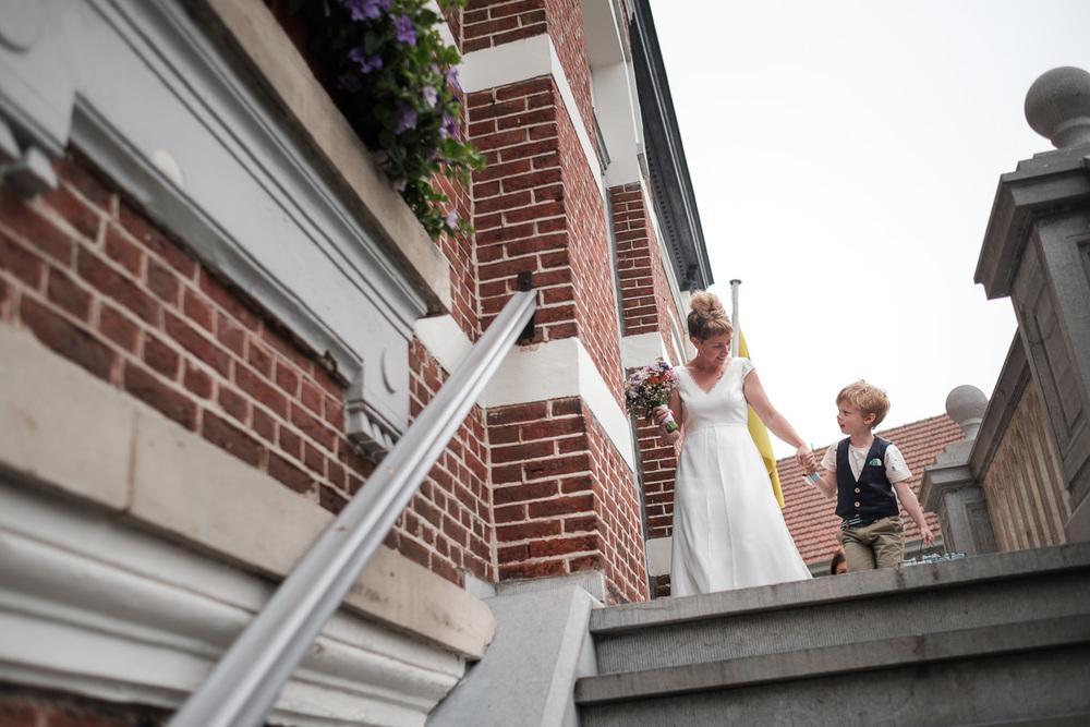De huwelijksfotografen van iso800 waren getuigen van het lang verwachte huwelijk van Lise en Elias. De hoogopgelopen verwachtingen werden vlotjes ingewilligd. Het heerlijk, vrolijke no-nonsens karakter van bruid en bruidegom en hun aandacht voor details scheen door in elk aspect van de dag. Van Tielen trokken we naar Wortel en de Bonte Beestenboel. Bruid en zoontje treden het gemeentehuis binnen.