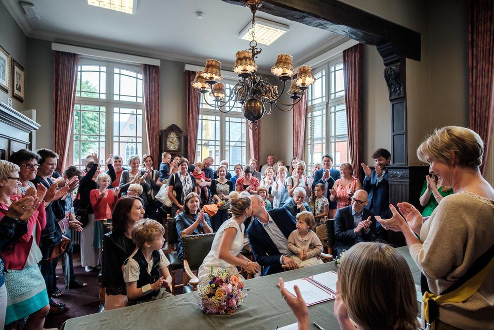 De huwelijksfotografen van iso800 waren getuigen van het lang verwachte huwelijk van Lise en Elias. De hoogopgelopen verwachtingen werden vlotjes ingewilligd. Het heerlijk, vrolijke no-nonsens karakter van bruid en bruidegom en hun aandacht voor details scheen door in elk aspect van de dag. Van Tielen trokken we naar Wortel en de Bonte Beestenboel. Bruid en bruidegom geven elkaar de eerste kus als man en vrouw in het gemeentehuid, de gasten applaudisseren.