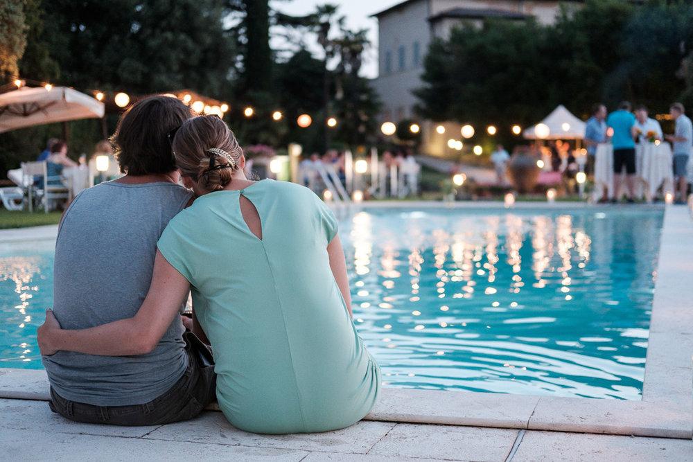 De huwelijksfotografen van iso800 zijn vandaag de dag nog in de wolken over dit uitzonderlijke huwelijk. Leatitia en Bart trouwden in het prachtige Toscaanse landschap, hadden een perfect gevolg volmaakt geflipte fasten en wisten de weergoden perfect te dirigeren. Maar dat alles was nog niets in vergelijking met de grootsheid van de verliefdheid die in hun ogen blonk. Een koppel kijkt verliefd uit over het zwembad in de avond.