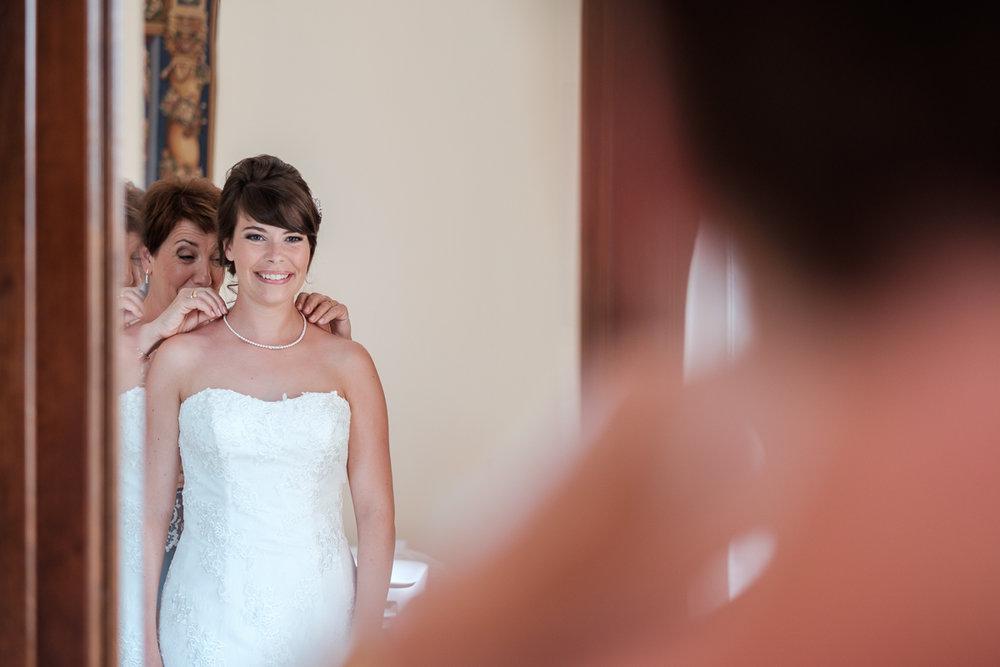 De huwelijksfotografen van iso800 zijn vandaag de dag nog in de wolken over dit uitzonderlijke huwelijk. Leatitia en Bart trouwden in het prachtige Toscaanse landschap, hadden een perfect gevolg volmaakt geflipte fasten en wisten de weergoden perfect te dirigeren. Maar dat alles was nog niets in vergelijking met de grootsheid van de verliefdheid die in hun ogen blonk. De bruid staat in haar bruidsjurk voor de spiegel. Haar moeder doet haar ketting om de hals.