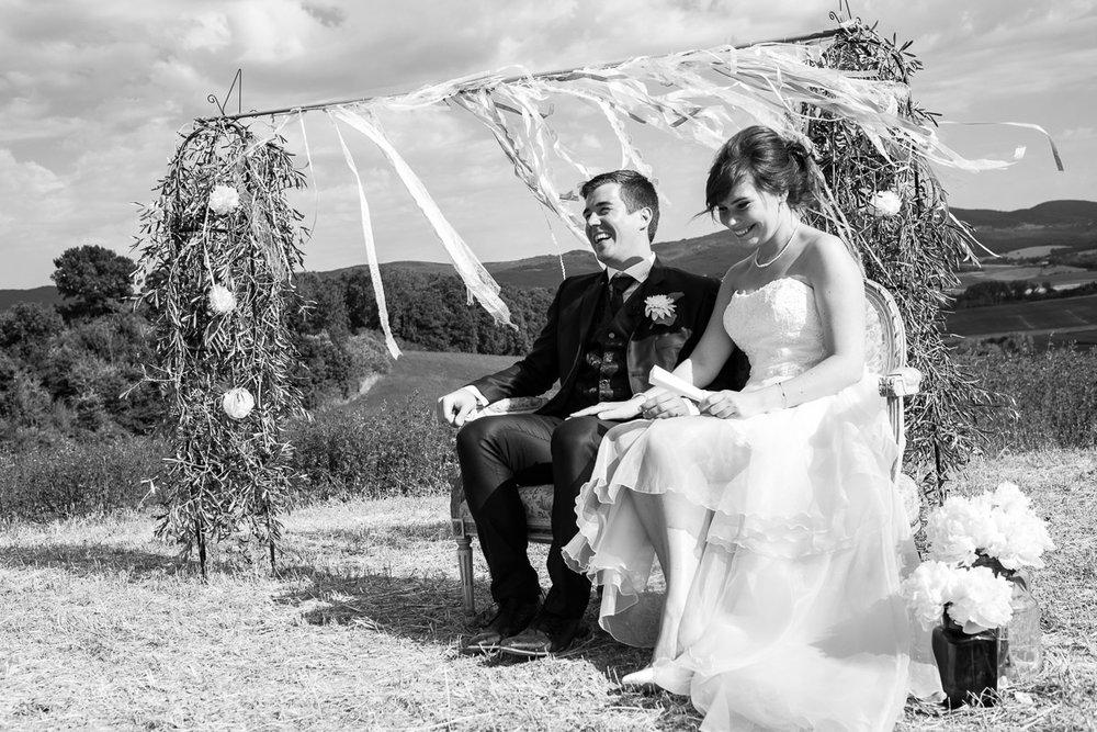 De huwelijksfotografen van iso800 zijn vandaag de dag nog in de wolken over dit uitzonderlijke huwelijk. Leatitia en Bart trouwden in het prachtige Toscaanse landschap, hadden een perfect gevolg volmaakt geflipte fasten en wisten de weergoden perfect te dirigeren. Maar dat alles was nog niets in vergelijking met de grootsheid van de verliefdheid die in hun ogen blonk. Zwart-wit foto van het koppel tijdens de ceremonie.