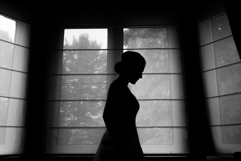 De huwelijksfotografen van iso800 zijn wederom te gast geweest bij een fantastisch feest, het huwelijk van Valérie en Steven. Vertrekken deden we in Brasschaat, vanwaar we naar het gemeentehuis in Kapellen reden, en nadien naar de kerk vlakbij. Het feest zelf ging dan weer door in het mooie Bebronna in Kallo. Zwart-wit foto van bruid die wacht bij het raam.