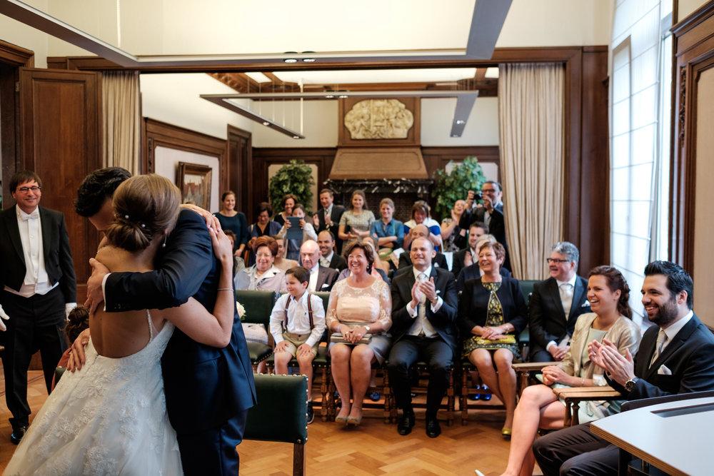 De huwelijksfotografen van iso800 zijn wederom te gast geweest bij een fantastisch feest, het huwelijk van Valérie en Steven. Vertrekken deden we in Brasschaat, vanwaar we naar het gemeentehuis in Kapellen reden, en nadien naar de kerk vlakbij. Het feest zelf ging dan weer door in het mooie Bebronna in Kallo. Sfeerbeeld van ceremonie in het gemeentehuis. Het koppel omhelst elkaar, de gasten applaudiseren.