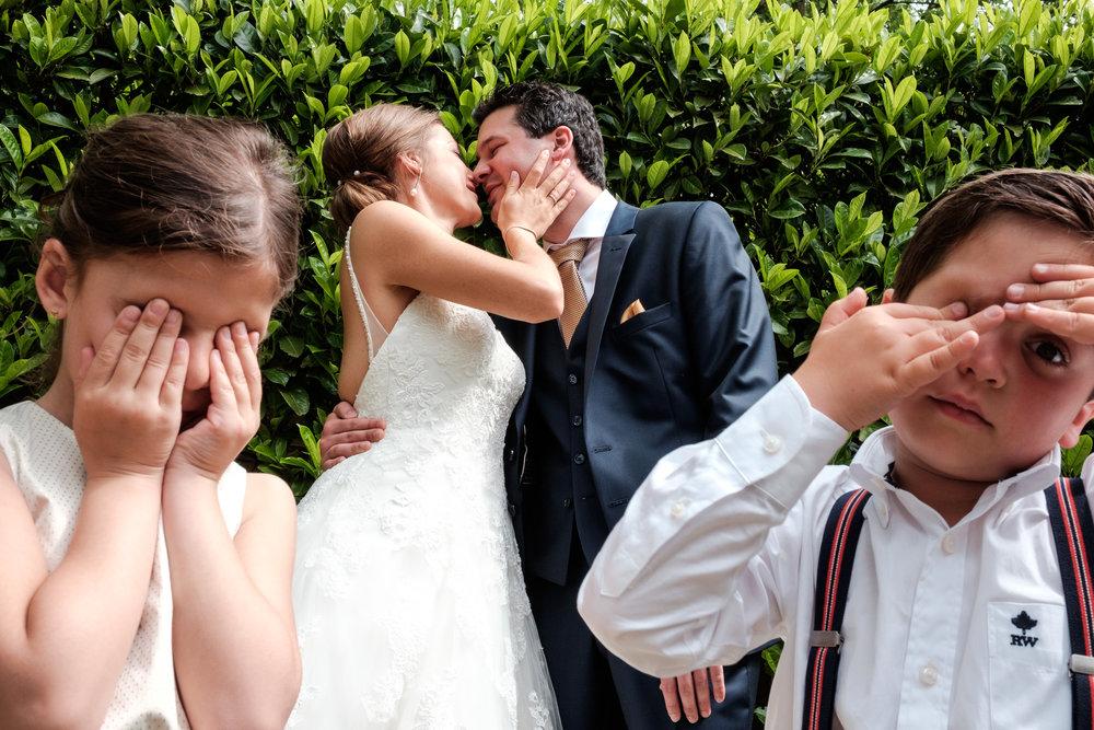 De huwelijksfotografen van iso800 zijn wederom te gast geweest bij een fantastisch feest, het huwelijk van Valérie en Steven. Vertrekken deden we in Brasschaat, vanwaar we naar het gemeentehuis in Kapellen reden, en nadien naar de kerk vlakbij. Het feest zelf ging dan weer door in het mooie Bebronna in Kallo. Foto van bruidspaar dat kust met kinderen op de voorgrond die hun ogen bedekken.