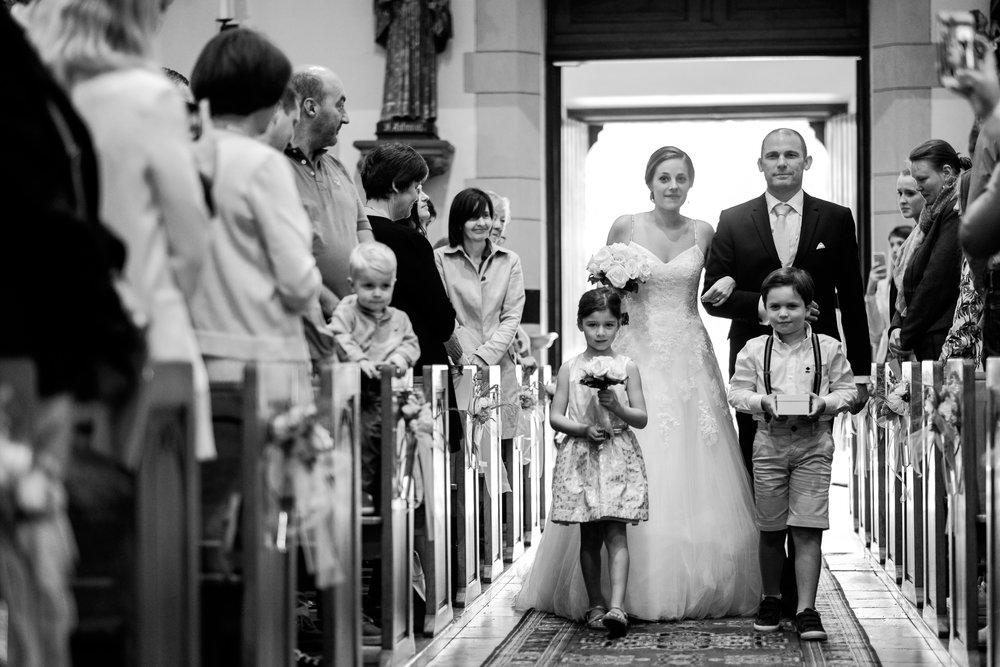 De huwelijksfotografen van iso800 zijn wederom te gast geweest bij een fantastisch feest, het huwelijk van Valérie en Steven. Vertrekken deden we in Brasschaat, vanwaar we naar het gemeentehuis in Kapellen reden, en nadien naar de kerk vlakbij. Het feest zelf ging dan weer door in het mooie Bebronna in Kallo. Bruid treedt de kerk binnen aan de arm van haar vader, voorgegaan door de twee bruidskinderen.