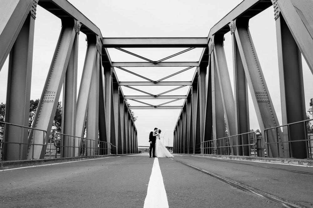 De huwelijksfotografen van iso800 zijn wederom te gast geweest bij een fantastisch feest, het huwelijk van Valérie en Steven. Vertrekken deden we in Brasschaat, vanwaar we naar het gemeentehuis in Kapellen reden, en nadien naar de kerk vlakbij. Het feest zelf ging dan weer door in het mooie Bebronna in Kallo. Zwart-wit foto van het koppel op een brug in de haven van Antwerpen.