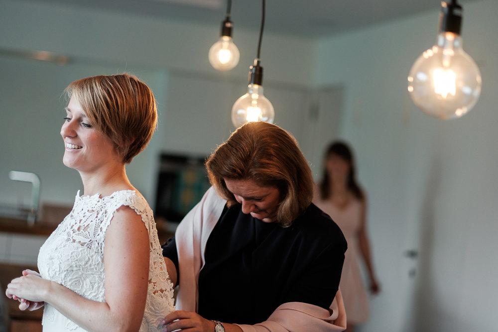 Fotoreportage van het huwelijk van de Sarah en Cédric. En dat was er één met stijl. Ze trouwden op de laatste nazomerdag van het jaar, vergezeld van een grote groep vrienden en familie Deze huwelijksfotograaf van iso800 was alvast gecharmeerd door de vrolijke no-nonse bruidegom en de prachtige, super-sympathieke bruid.De knoopjes op de rug van de bruid worden geknoopt door haar moeder.