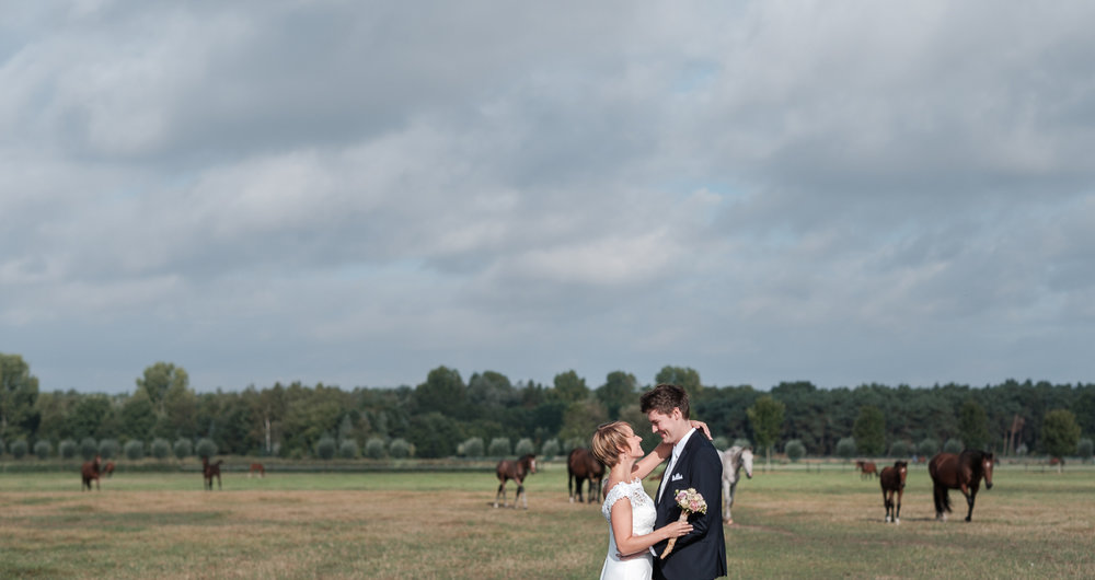 Fotoreportage van het huwelijk van de Sarah en Cédric. En dat was er één met stijl. Ze trouwden op de laatste nazomerdag van het jaar, vergezeld van een grote groep vrienden en familie Deze huwelijksfotograaf van iso800 was alvast gecharmeerd door de vrolijke no-nonse bruidegom en de prachtige, super-sympathieke bruid. Foto tijdens de shoot, koppel tegen een achtergrond van een landschap vol paarden.