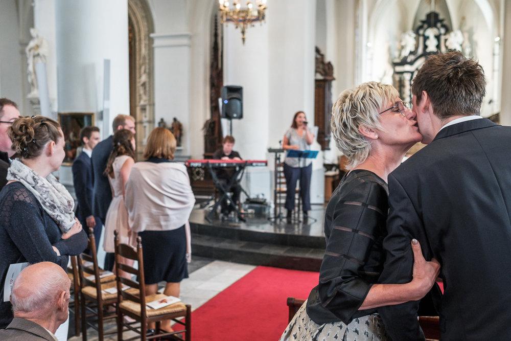 Fotoreportage van het huwelijk van de Sarah en Cédric. En dat was er één met stijl. Ze trouwden op de laatste nazomerdag van het jaar, vergezeld van een grote groep vrienden en familie Deze huwelijksfotograaf van iso800 was alvast gecharmeerd door de vrolijke no-nonse bruidegom en de prachtige, super-sympathieke bruid. Moeder geeft bruidegom een zoen aan haar zoen bij het einde van het gangpad.