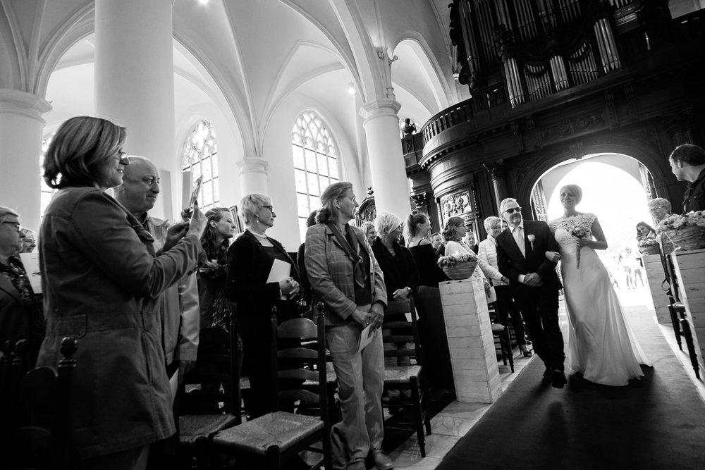 Fotoreportage van het huwelijk van de Sarah en Cédric. En dat was er één met stijl. Ze trouwden op de laatste nazomerdag van het jaar, vergezeld van een grote groep vrienden en familie Deze huwelijksfotograaf van iso800 was alvast gecharmeerd door de vrolijke no-nonse bruidegom en de prachtige, super-sympathieke bruid. De bruidegom wordt naar het altaar begeleidt door haar vader.