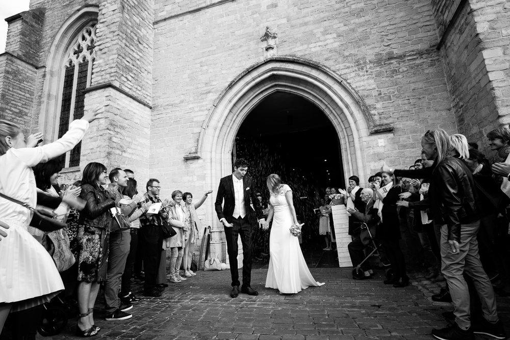 Fotoreportage van het huwelijk van de Sarah en Cédric. En dat was er één met stijl. Ze trouwden op de laatste nazomerdag van het jaar, vergezeld van een grote groep vrienden en familie Deze huwelijksfotograaf van iso800 was alvast gecharmeerd door de vrolijke no-nonse bruidegom en de prachtige, super-sympathieke bruid. Het koppel stapt de kerk buiten en wordt verrast door de omstanders.