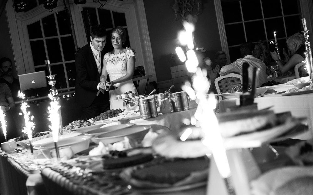 Fotoreportage van het huwelijk van de Sarah en Cédric. En dat was er één met stijl. Ze trouwden op de laatste nazomerdag van het jaar, vergezeld van een grote groep vrienden en familie Deze huwelijksfotograaf van iso800 was alvast gecharmeerd door de vrolijke no-nonse bruidegom en de prachtige, super-sympathieke bruid. Het koppel snijdt de huwelijkstaart aan.