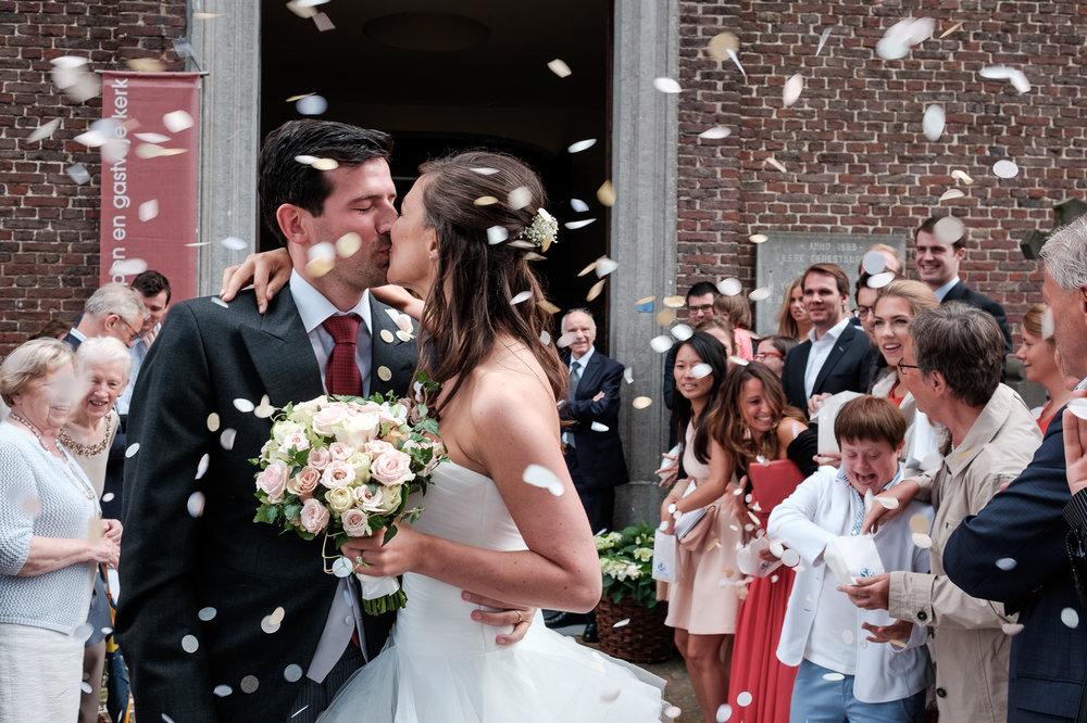 Sofie en Bernard hadden het privilege om in de tuin van de ouders van de bruidegom hun trouwfeest te houden. Geen slecht idee, zo bleek. De huwelijksfotografen van iso800 waren gelukkige getuigen. Het bruidspaar geeft elkaar een kus voor de ingang van de kerk na de plechtigheid. De omstanders gooien confetti.